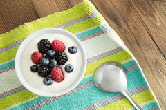 Delicious yogurt and fresh berries for breakfast. With strawberries, blackberries and blueberries served on a colourful striped placemat Stock Images