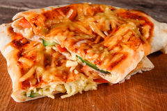 Delicious yummy slices of pizza calzone, close up. Delicious yummy and fresh slices of italian pizza calzone stuffed with bacon, tomato, cheese and cucumber Stock Image