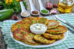 Delicious zucchini fritters on plate, close-up. Delicious zucchini fritters sprinkled with finely chopped chives on platter with sour cream, on old dark wooden Royalty Free Stock Photo
