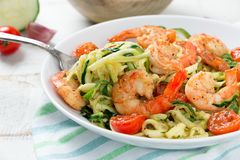 Delicious zucchini noodles with cherry tomato and prawns. Zucchini noodles sauteed with tomato cherry and prawns in a dish on a rustic white wooden table. Close stock photography