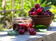 DeliciousCherry jam with fresh cherry on the background of the garden. Rustic weathered wood background. Cherry jam with fresh cherry on the background of the Royalty Free Stock Images