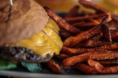 Deliciouse cheeseburger z świeżymi batatów dłoniakami fotografia royalty free