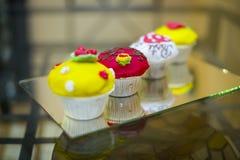 Fyra läckra färgrika muffiner Arkivfoton