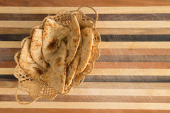 Deliciously baked naan flatbread slices in basket on cutting board. Delicious crusty whole grain naan flatbread slices, a leavened bread cooked in a tandoor clay Royalty Free Stock Photos