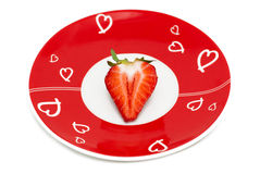 Deliciously half a red strawberry romantic plate Royalty Free Stock Photography