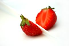 Deliciously red strawberries cut into half. With white ceramic knife (on white plate Stock Photo