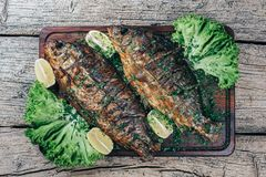 A deliciously roasted carp on a grill, presented on a wooden board, and along the leaves of green salad and pieces of lemon.  stock photo