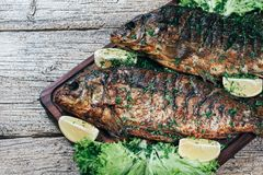 A deliciously roasted carp on a grill, presented on a wooden board, and along the leaves of green salad and pieces of lemon.  stock photography