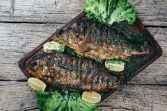 A deliciously roasted carp on a grill, presented on a wooden board, and along the leaves of green salad and pieces of lemon.  royalty free stock photo