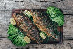A deliciously roasted carp on a grill, presented on a wooden board, and along the leaves of green salad and pieces of lemon.  royalty free stock photography