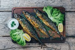 A deliciously roasted mackerel on a grill, presented on a wooden board, and along the leaves of green salad and pieces of lemon.  stock image