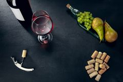 A bottle and a glass of red wine with fruits over dark stone background. Delicisious and tasty food and drink. A bottle and a glass of red wine with fruits over royalty free stock photography
