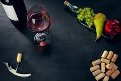 A bottle and a glass of red wine with fruits over dark stone background. Delicisious and tasty food and drink. A bottle and a glass of red wine with fruits over royalty free stock photo