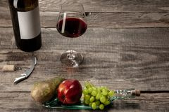 A bottle and a glass of red wine with fruits over dark stone background. Delicisious and tasty food and drink. A bottle and a glass of red wine with fruits over royalty free stock image