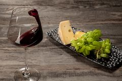 A bottle and a glass of red wine with fruits over wooden background. Delicisious and tasty food and drink. A bottle and a glass of red wine with fruits over royalty free stock images