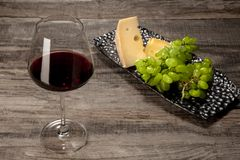 A bottle and a glass of red wine with fruits over wooden background. Delicisious and tasty food and drink. A bottle and a glass of red wine with fruits over royalty free stock image