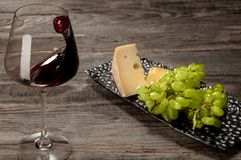 A bottle and a glass of red wine with fruits over wooden background. Delicisious and tasty food and drink. A bottle and a glass of red wine with fruits over stock image