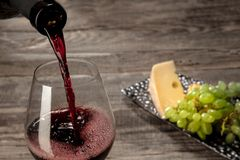A bottle and a glass of red wine with fruits over wooden background. Delicisious and tasty food and drink. A bottle and a glass of red wine with fruits over royalty free stock photo