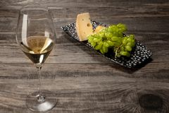 A bottle and a glass of white wine with fruits over wooden background. Delicisious and tasty food and drink. A bottle and a glass of white wine with fruits over stock photos