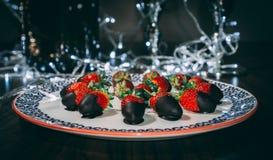 DeliciStrawberries på plattan som täckas med den chocolateous hemlagade kakan på tabellen royaltyfri foto