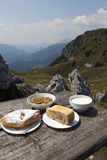 Delicius food on a wooden table high in the mountains. Delicius home made organic food on a wooden table high in the mountains, selective focus on food Royalty Free Stock Images