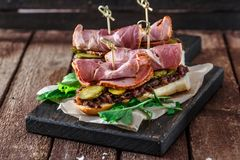 Delicius sandwiches with smoked pork, cucumbers and onion on a black wooden board.  Stock Photo