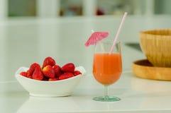 Delicous jordgubbefruktsaft i ett exponeringsglas och nytt Royaltyfri Bild