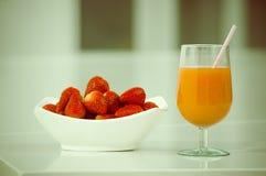 Delicous jordgubbefruktsaft i ett exponeringsglas och nytt Arkivfoton