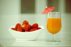 Delicous jordgubbefruktsaft i ett exponeringsglas och nytt Arkivfoto