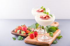 Delicous and nutritious double color colour strawberry desserts with mint and diced sarcocarp topping isolated with airy blue. Background, copy space, close up royalty free stock photo