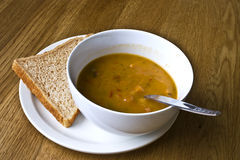 soup and bread. A photo of a bowl of vegetable soup and a slice of brown bread Stock Photo