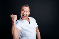 Delighetd handsome man smiling. Yes man. Cheerful delighted handsome senior man expressing jubilation and using his gestures while smiling royalty free stock photos
