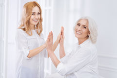 Delighetd loving mother and her adult daughter resting at home Stock Image