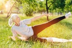Delighetd smiling aged woman doing sport exercises stock image