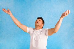 Delight. Portrait of handsome man raising his arms in delight over blue background stock photo