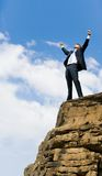 Delight. Photo of joyful businessman raising his arms upwards while standing on the rocky cliff stock photography