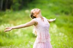 Delight. Photo of relaxing woman with closed eyes and stretched arms expressing delight outdoors royalty free stock photography