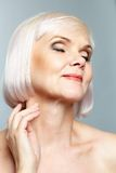 Delight. Portrait of aged female in delight over grey background royalty free stock images