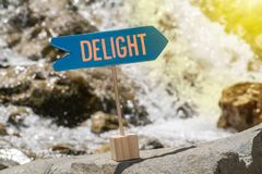 Delight sign board on rock. Delight wooden sign board arrow on rock , river and sun shine background stock photo