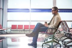 Delighted adult traveler is resting at international airport Stock Image