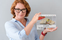 Delighted adult woman holding tablet Royalty Free Stock Image