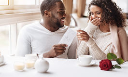 Delighted African American woman receiving a present from her boyfriend. Pleasant moment. Cheerful beautiful surprised African American women sitting in the cafe Stock Image