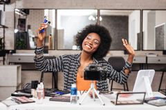 African american woman with curly hair feeling wonderful. Delighted. African american woman wearing a trendy shirt feeling wonderful while demonstrating a royalty free stock photos