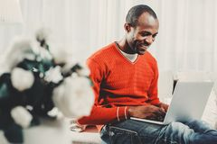 Glad man concentrating on computer screen. Delighted african guy using notebook inside. He is looking at monitor with joy. Copy space in left side Stock Photos