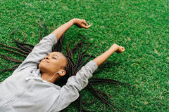 Delighted afro-american teenager is enjoying music while laying on the grass and raising hands. Royalty Free Stock Photo