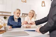 Delighted aged couple signing loan contract at home Royalty Free Stock Image
