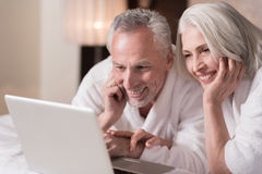 Delighted aged couple watching a movie at home stock image