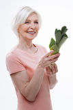 Delighted aged female posing with caulis of leek Stock Photos