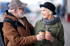 Delighted aged man and woman are drinking espresso on street. Cheers. Profile of optimistic happy senior couple are standing together outdoors while clinking royalty free stock photography