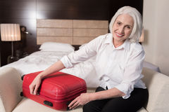 Delighted aged woman gathering her luggage Royalty Free Stock Photography